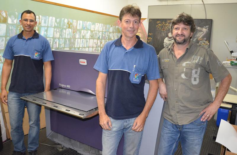 Robson dos Santos, Tércio Ternitani e Renato de Oliveira juntos do primeiro CtP Kodak adquirido pela Compulaser: um modelo Magnus 400
