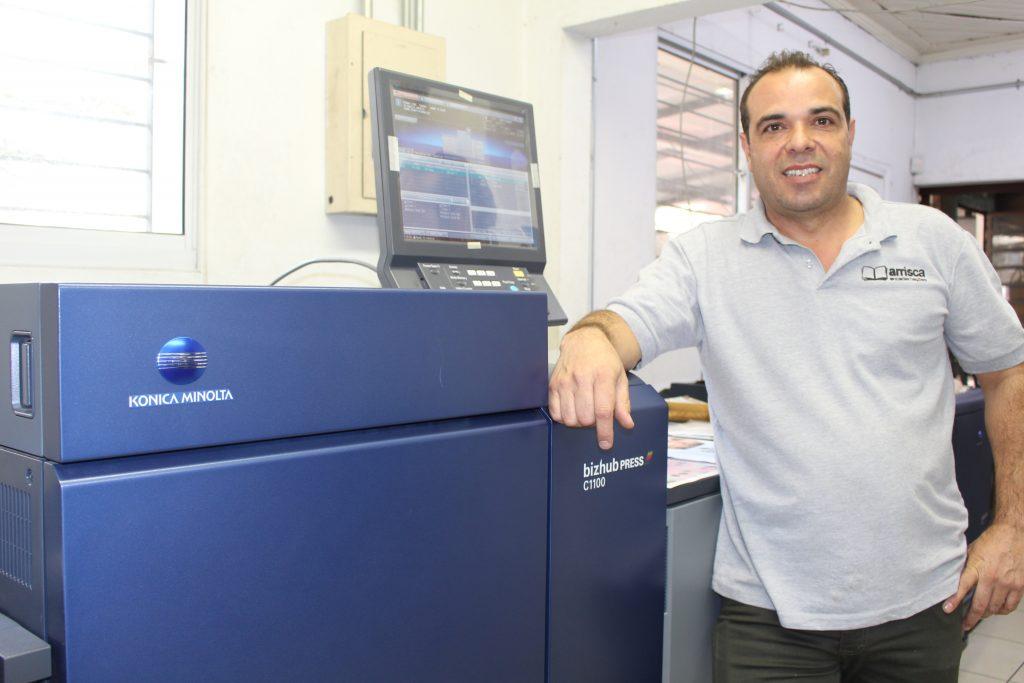 Sr. Adenilson Pereira ao lado do modelo bizhub PRESS C1100